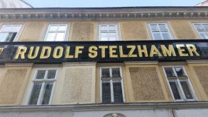 goldener Schriftzug Rudolf Stelzhamer an einem Haus