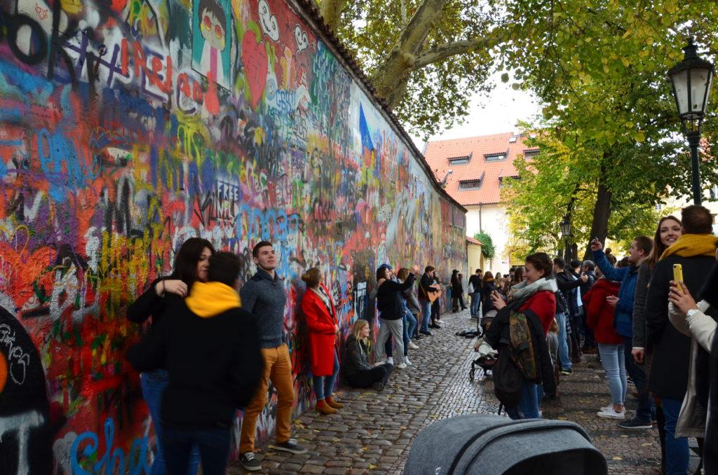Menschen posieren vor einer Graffiti-Wand